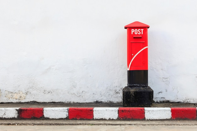 Old red postbox on the street. over light