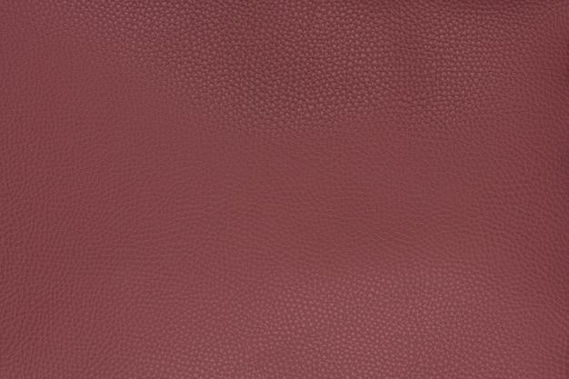 中粒の織り目加工の背景に古い赤い滑らかな天然皮革