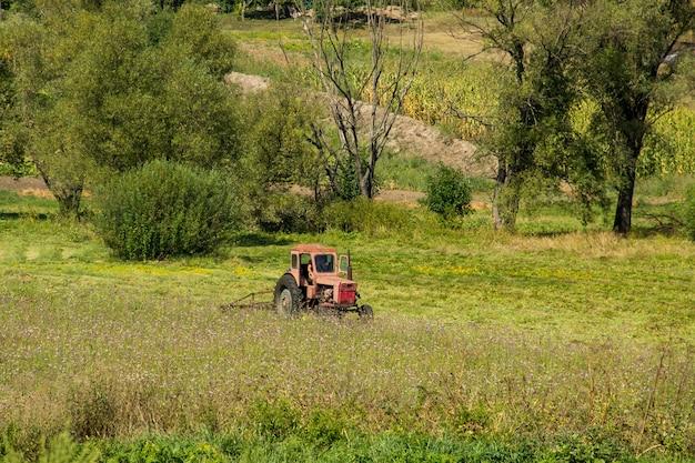 초원에서 건초를 하는 오래 된 빨간 트랙터