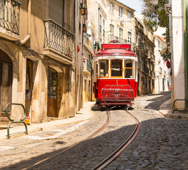 Old red tram on narrow european street in sunny days