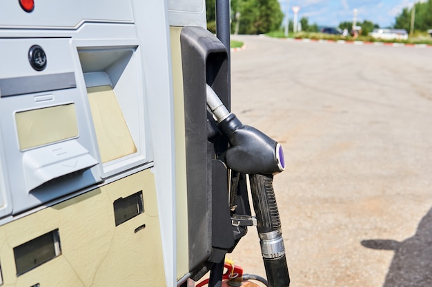 Old refueling nozzle in a dispenser slot somewhere at a roadside gas station