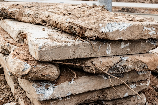 Old reinforced concrete road slabs stacked on a construction site for later use. temporary road surface.