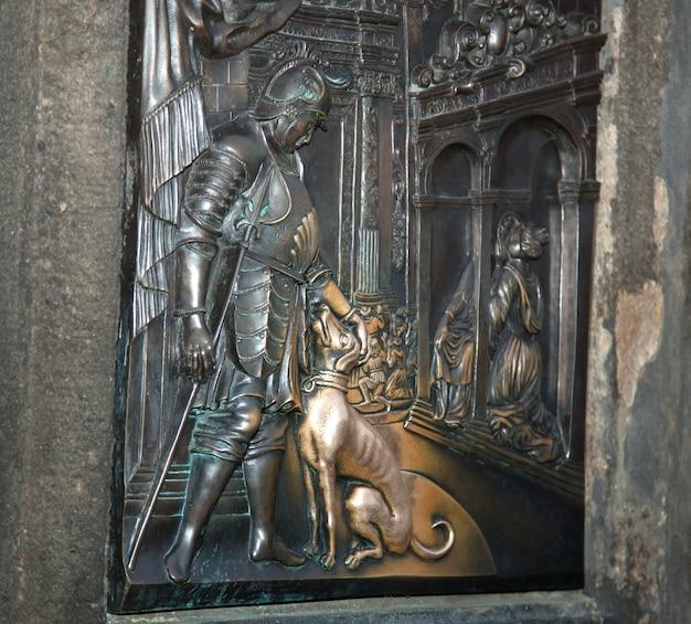 Старый рельеф под статуей святого иоанна непомуцкого на карловом мосту в праге, чешская республика. по легенде прикосновение приносит удачу.