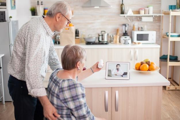 オンラインビデオ通話を介して医師と処方箋をチェックする老夫婦。キッチンでラップトップを使用している医師とのビデオ会議。高齢者のためのオンライン健康相談薬の病気のアドバイス