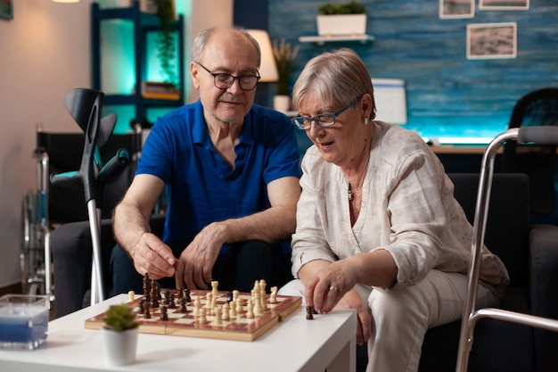 Old retired husband and wife enjoying chess game