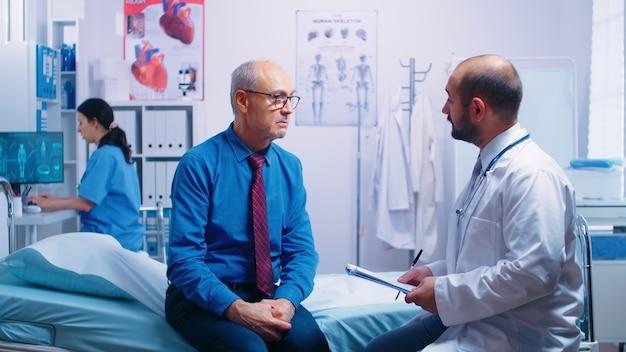 Vecchi uomini in pensione nella moderna clinica privata che rispondono al questionario del medico seduto sul letto d'ospedale. paziente invecchiato malato che cerca consiglio medico per la prevenzione delle malattie dal medico generico in pri . moderna