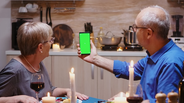 Old retired senior couple holding mockup phone at dinner. aged people looking at green screen template chroma key isolated smart phone display using techology internet sitting at the table in kitchen.