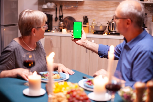 Old retired senior couple holding mockup phone at dinner. aged people looking at mockup template chroma key isolated smart phone display using techology internet sitting at the table in kitchen.