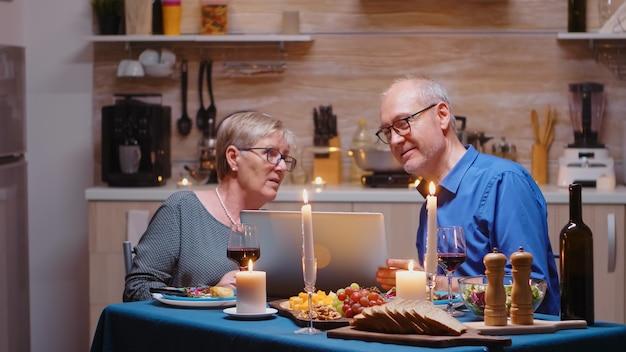 Старые пенсионеры старшие пары с помощью ноутбука на кухне. пожилые люди сидят за столом, просматривают, ищут, используют ноутбук, технику, интернет, празднуют свой юбилей в столовой.