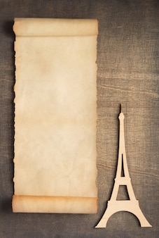 Old retro aged paper parchment  and eiffel tower toy at wooden background