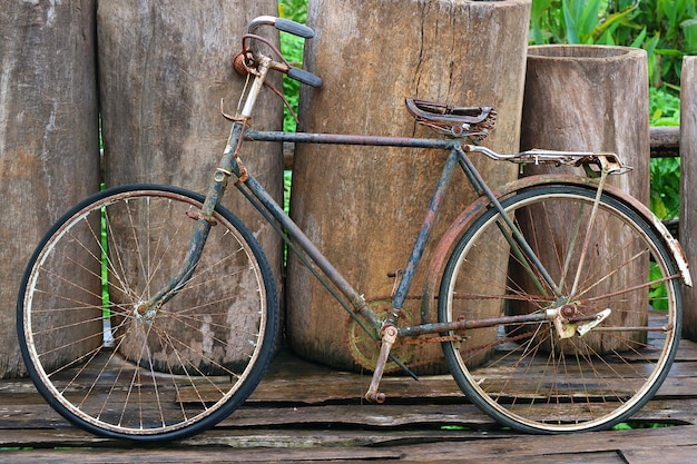 An old retro antique vintage bicycle leaning against wooden fence