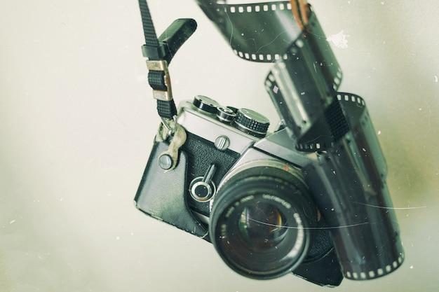 壁の背景にフィルムと古いレトロカメラ