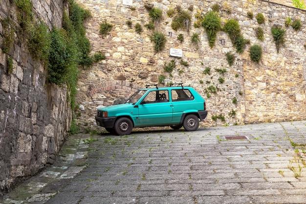오래된 중세 마을 몬테풀치아노 이탈리아의 거리에 있는 중세 벽돌 벽에 대한 오래된 복고풍 자동차