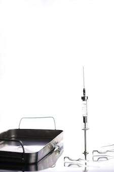 테이블에 있는 오래된 복고풍 금속 의료 주사기 및 액세서리