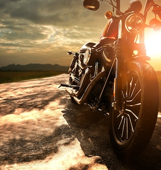 Old retro motorcycle traveling on country road against beautiful light of sunset sky