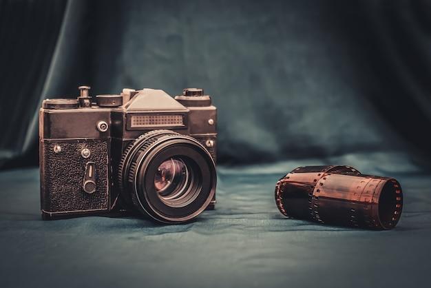 古いレトロな写真のカメラと巻かれた写真フィルムは、濃い緑色の背景のテーブルに