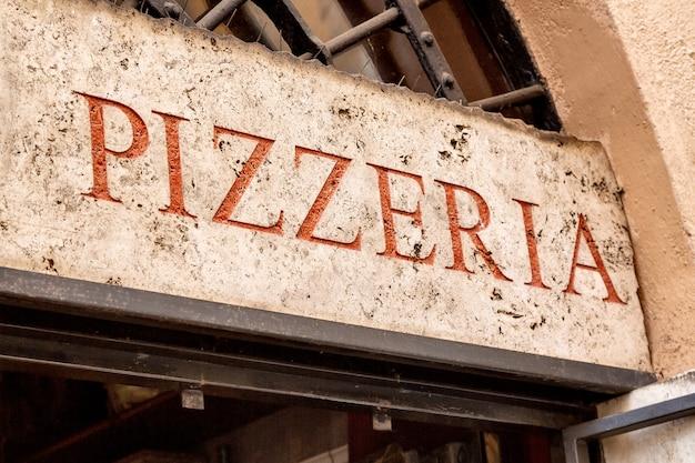 Old retro pizzeria signboard in rome, italy.