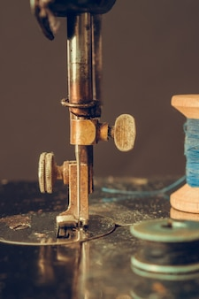 Old retro sewing machine and details of needle close-up of thread
