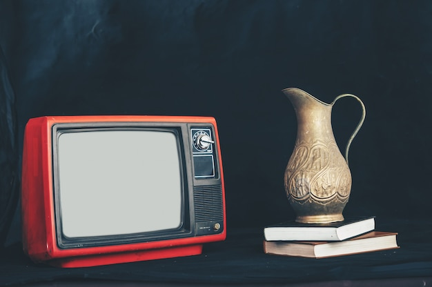 Old retro tv by placing flower vases on books