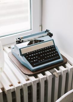 Старая ретро пишущая машинка на подоконнике.