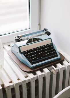 Old retro typewriter on the windowsill.