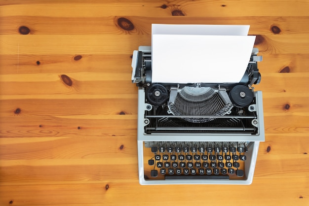 Old retro typewriter on wooden desk.