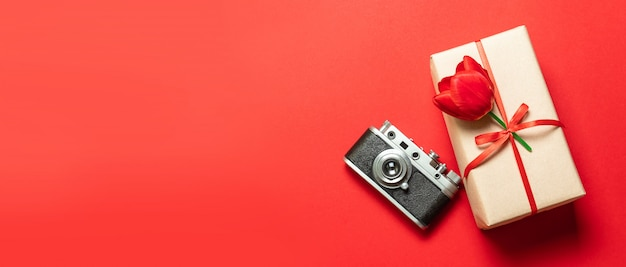 Old retro vintage camera, gift box with red ribbon on red