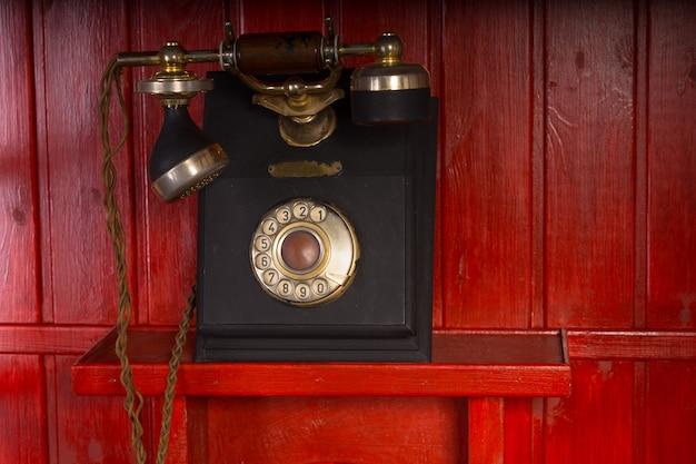 빨간 나무 벽에 핸드셋과 크래들이 장착된 오래된 복고풍 빈티지 회전식 전화 기기