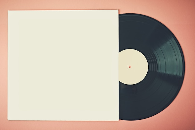 Old retro vinyl disc in paper case on pink