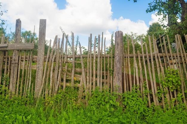 마을 집 앞 좁은 보드로 만든 오래 된 구루병 나무 울타리