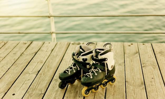 Old roller skates on a beach terrace against the sea