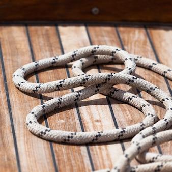 Старая веревка на деревянной палубе лодки. квадратный выстрел