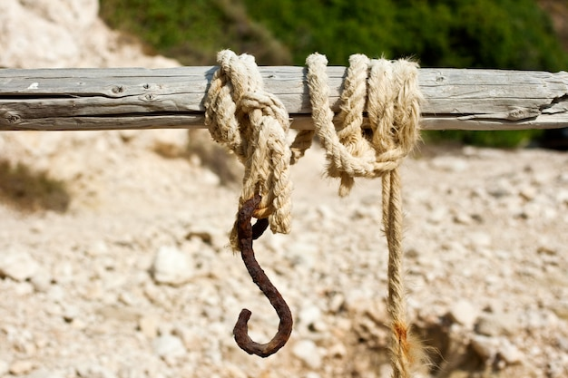 Old rope with the hook tied to a wooden pole