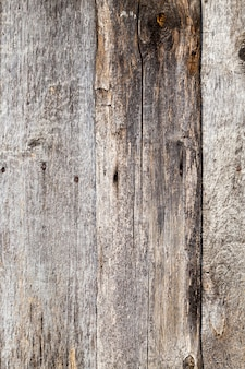 Old rotting wooden planks, part of the wall of the building in the village