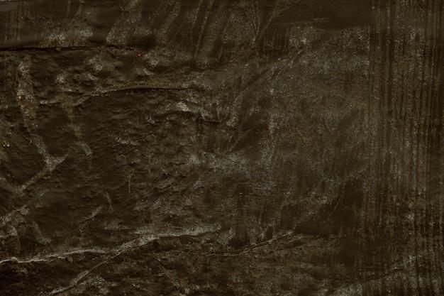 Старая грубая литая окрашенная бетонная стена с грязной темной краской