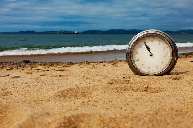 Старые круглые корабельные часы на песке летом у моря