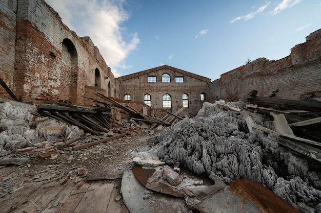 Старое разрушенное кирпичное здание, стены. без крыши, под открытым голубым небом. груды мусора внутри.