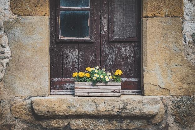 黄色いマリーゴールドの花と小さな白いヒナギクでいっぱいの木製の鍋と古い田舎の窓