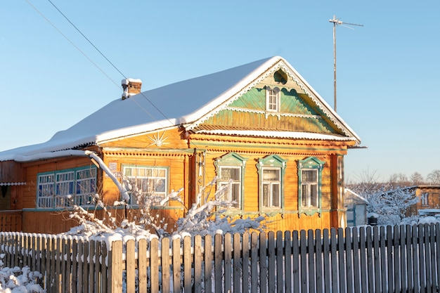 Old rural yellow wooden house iin winter sunny day