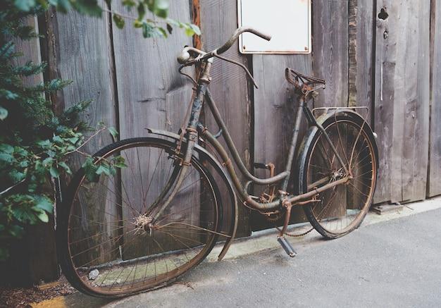 通りに立っている古い錆びた自転車