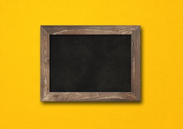 黄色の背景に分離された古い素朴な黒板