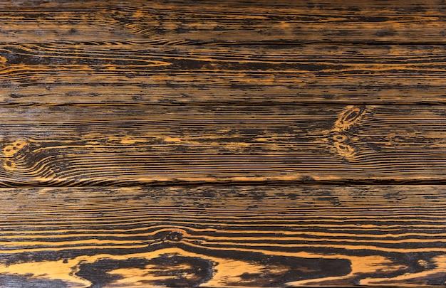 古い素朴な木製のテーブルまたは床の背景のテクスチャと平行な板、暗い広葉樹でマークされた木目模様