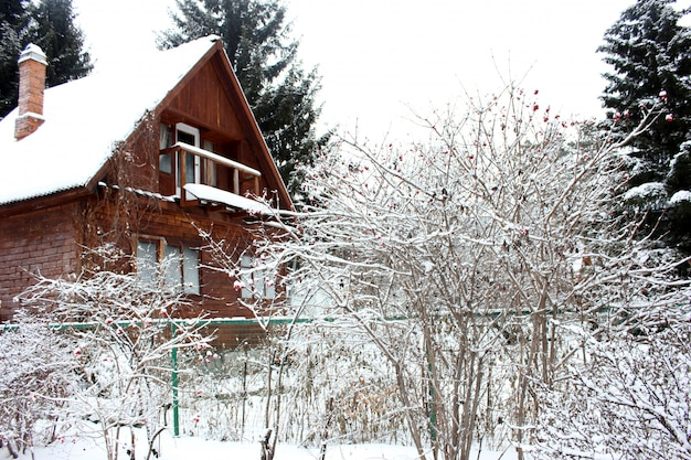 Old rustic wooden house in the snowy forest in winter