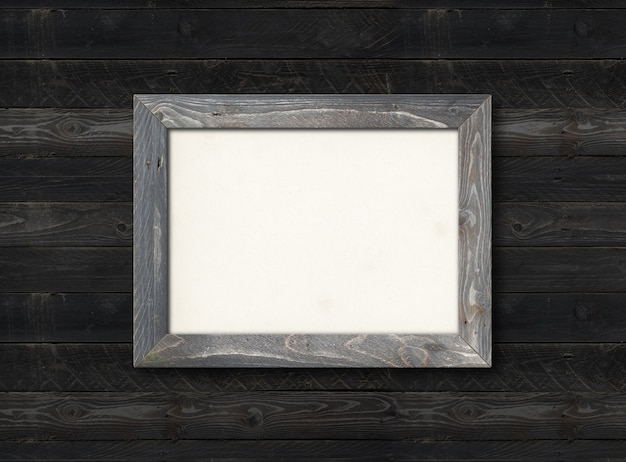 Old rustic wooden picture frame hanging on a black wood wall. horizontal picture. blank mockup template