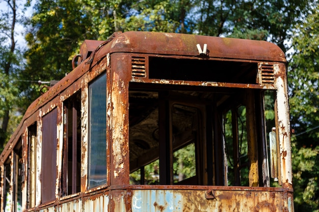 Old rusty abandoned tram outdoors at sunny day.