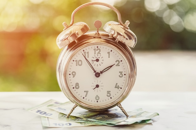 Old and rusty alarm clock and 100 hundredth euro banknotes