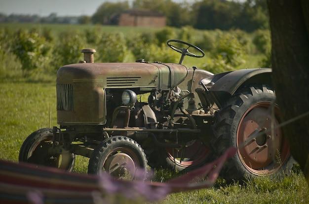 過去50年間に作られた労働時間からの古いさびた、台無しにされた農業用トラクター。フィールドでの労働生活のシンボル。