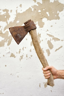 Старый ржавый топор в руке человека против потертой стены.