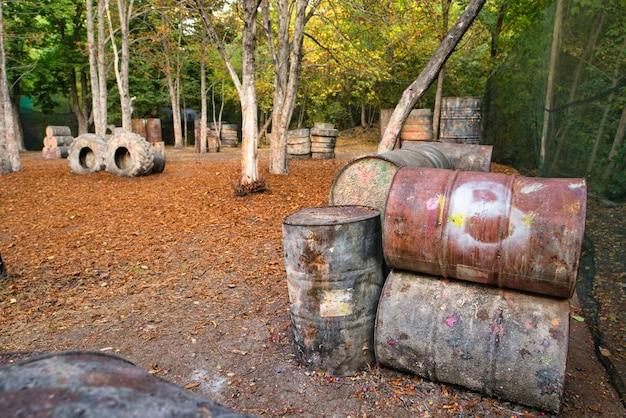 Старые ржавые бочки и поврежденные шины на пейнтбольной базе, где прячутся возбужденные игроки