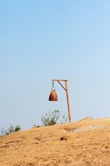 Old rusty bell with dry grassland and wild with blue sky on the valley mountain at doi pha tang hill in thailand